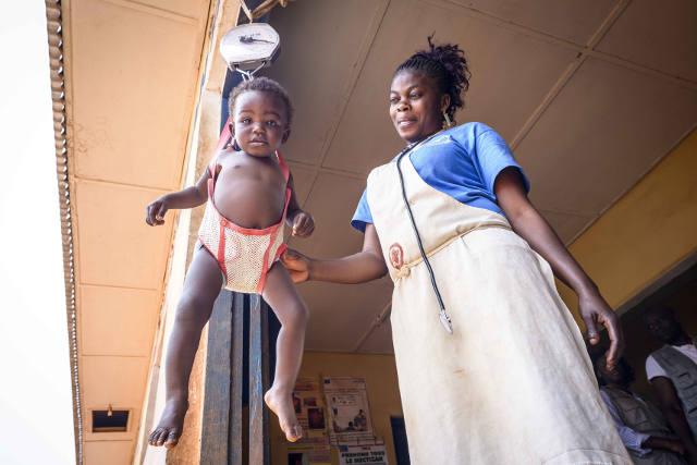 """Consolation Bavelila, 13 mois, est un bébé """"ANJE"""" - allaitée exclusivement au sein par sa mère Bibiche, elle est désormais un bébé en bonne santé, comme le montre sa pesée au Centre de Santé Kuakua de Vunda (Bas-Congo)"""